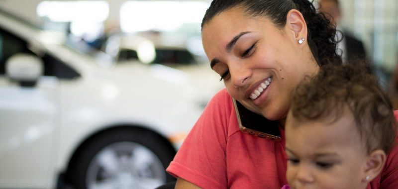 mother-and-daughter-purchasing-minivan-at-dealership-on-the-phone-to-confirm-a-bank-loan_t20_pR4wYN